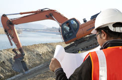 Foreman construction and excavator driver working. Foreman construction in front of excavator checking plan stock photography