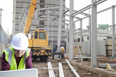 Foreman construction site using laptop. With construction background and worker Royalty Free Stock Photo