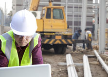 Foreman construction site using laptop. With construction background and worker Stock Image
