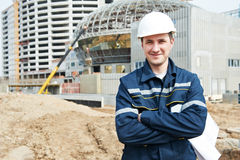 Foreman at construction site with working drawings. One happy engineer builder foreman with blueprint plan working deawing at construction site Royalty Free Stock Photography