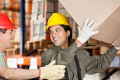Foreman With Coworker Lifting Cardboard Box At Royalty Free Stock Photo
