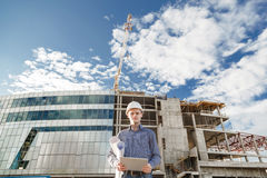 Foreman with digital tablet supervising the project at the construction. Royalty Free Stock Image