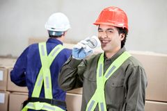 Foreman Drinking Coffee While Colleague Working At Stock Image