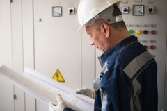Foreman electrician examines the working draft next to the dashboard. Energy and electrical safety.  stock photo
