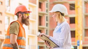 Foreman established supply of building materials. Expert and builder communicate about supply building materials stock photo