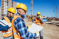 Foreman examining a building plan while standing at construction site. With colleagues royalty free stock photography
