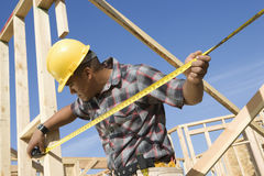 Foreman Examining Framework At Site. Foreman examining framework with measure tape at construction site stock image