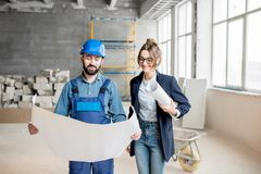 Builder with businesswoman at the construction site. Foreman expertising the structure with businesswoman holding a blueprints at the construction site indoors stock photos