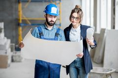 Builder with businesswoman at the construction site. Foreman expertising the structure with businesswoman holding a blueprints at the construction site indoors royalty free stock photo
