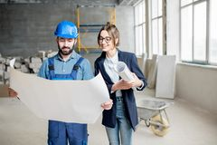 Builder with businesswoman at the construction site. Foreman expertising the structure with businesswoman holding a blueprints at the construction site indoors stock images