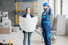 Builder with businesswoman at the construction site. Foreman expertising the structure with businesswoman holding a blueprints at the construction site indoors stock photography