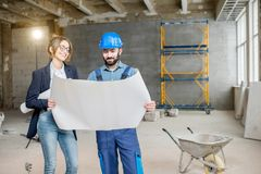Builder with businesswoman at the construction site. Foreman expertising the structure with businesswoman holding a blueprints at the construction site indoors stock image