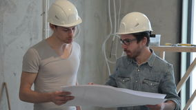 Foreman explains working of the plan of repair in room on paper. Two people in white protective helmets stand among the premises in which construction work is stock video