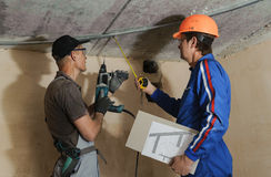 Foreman gives instructions to workers. As a drywall ceiling mount Stock Images