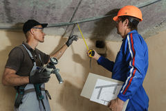 Foreman gives instructions to workers. As a drywall ceiling mount Royalty Free Stock Photo