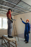 Foreman gives instructions to workers. As a drywall ceiling mount Stock Photo
