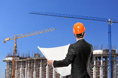 Foreman holding a blueprints on construction site. A foreman in a black suit holding a blueprints and looking towards the construction site stock photo