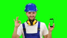Foreman holds a phone in his hands and shows a thumbs up. Green screen. Mock up. Foreman in a suit and a helmet holds the phone in his hands and shows a thumbs stock video