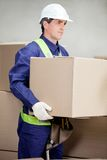 Foreman Lifting Cardboard Box At Warehouse Royalty Free Stock Photo