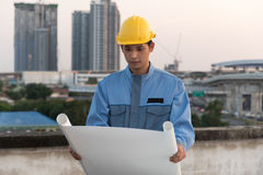 Foreman looking at blueprint at a construction site. Over building background stock photography