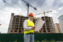 Foreman looking on blueprints at building site Royalty Free Stock Photography