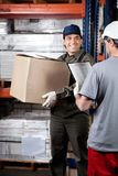 Foreman Looking At Supervisor With Clipboard. Foreman with cardboard box looking at supervisor holding clipboard at warehouse Royalty Free Stock Photos