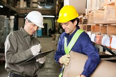 Foreman Looking At Supervisor Writing Notes. Young foreman looking at supervisor writing notes in warehouse Stock Photos