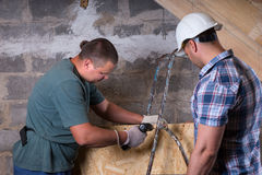 Foreman Monitoring Worker Using Drill in New Home Royalty Free Stock Photos
