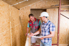 Foreman with Plans Monitoring Worker In New Home Royalty Free Stock Photos