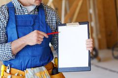 Foreman pointing at folder plate Royalty Free Stock Photography