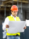 Foreman reading blueprints against scaffolding at building site Royalty Free Stock Image