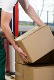 Foreman's hands lifting box at storehouse Stock Photography
