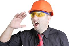 Foreman shouts. The young builder in a building helmet shouts on the isolated white background Stock Photo