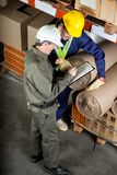 Foreman With Supervisor Writing Notes At Warehouse. High angle view of young foreman with supervisor writing notes at warehouse Stock Photo