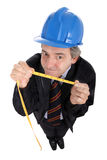 Foreman with tape measure. A foreman with tape measure and a blue hardhat isolated on white background Royalty Free Stock Photo