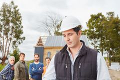 Foreman with team. At construction site royalty free stock photo