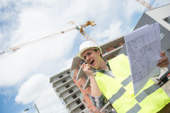 Foreman using walkie-talkie and yell on construction site Stock Photography