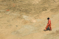 Foreman walks through construction site. Lone foreman inspects construction work site Royalty Free Stock Image