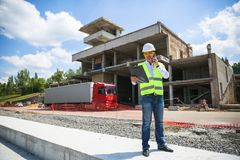 Foreman in working uniform expertising the structure standing with folder at the construction site. royalty free stock images