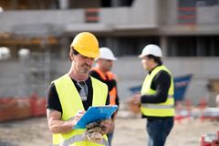 Foreman at work on construction site. Checking his notes and drawing plan on clipboard stock photography