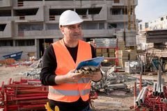 Foreman at work on construction site. Checking his notes and drawing plan on clipboard stock images