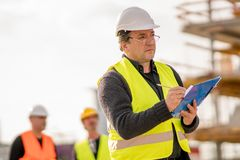 Foreman at work on construction site. Checking his notes and drawing plan on clipboard royalty free stock photography