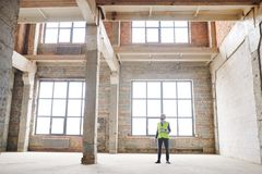 Foreman at work. Young contemporary foreman or contractor in helmet and uniform standing in unfinished building while checking work of builders stock images