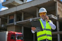Foreman in working uniform expertising the structure standing with folder at the construction site. royalty free stock photo
