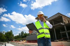 Foreman in working uniform expertising the structure standing with folder at the construction site. stock images