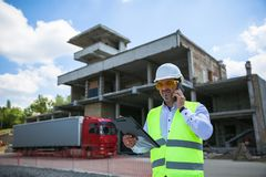 Foreman in working uniform expertising the structure standing with folder at the construction site. stock photography