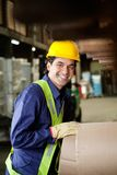 Foreman Working At Warehouse. Portrait of happy young foreman in uniform and hardhat working at warehouse Stock Image