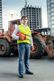 Foreman in yellow  jacket posing next to bulldozer on building s Stock Image
