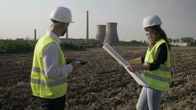 Foreman and young female engineer discussing project details using tablet pc and blueprint outdoor near petrochemical factory  -. Foreman and young female stock video footage