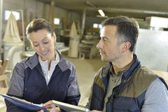 Foreman and young woman in workshop Stock Photos